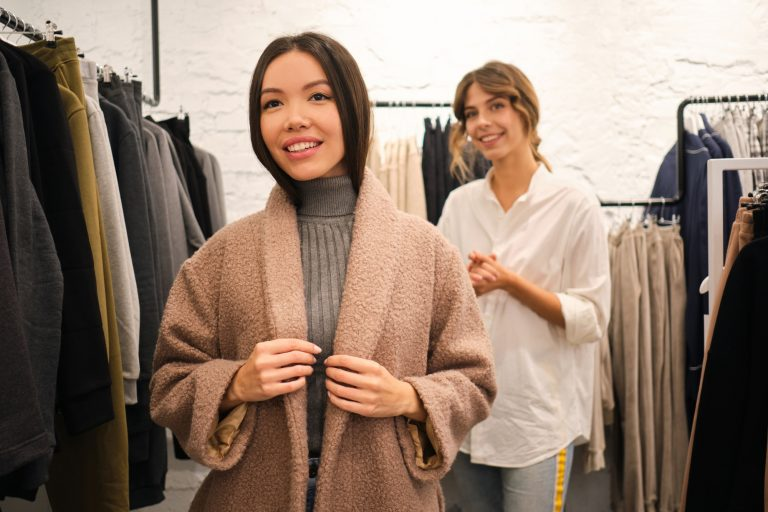 Beautiful stylish Asian girl joyfully trying on new casual coat in clothes store
