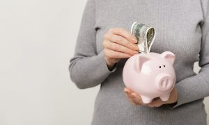Unrecognizable woman putting cash into piggy bank