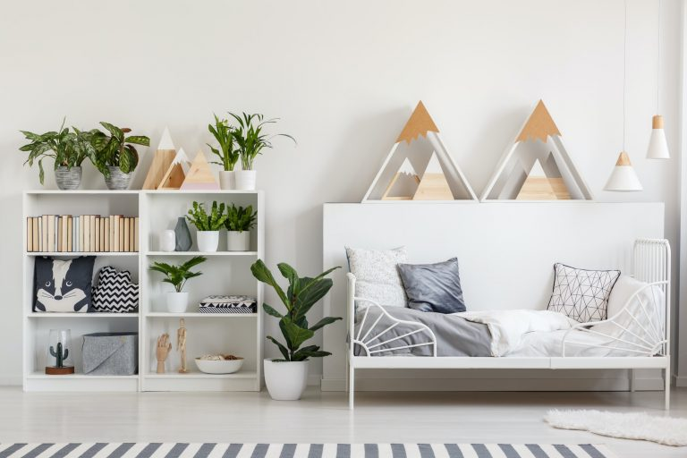 Wooden rack with books, fresh plants and cushions in white bedro
