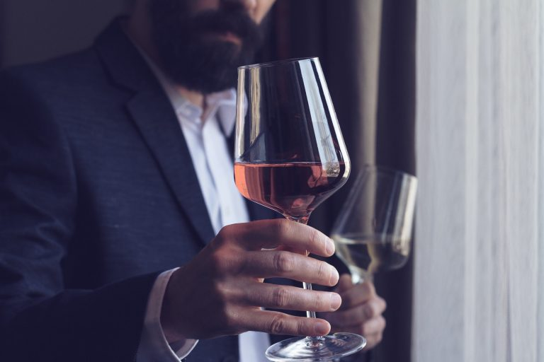 man offering a glass of rose wine