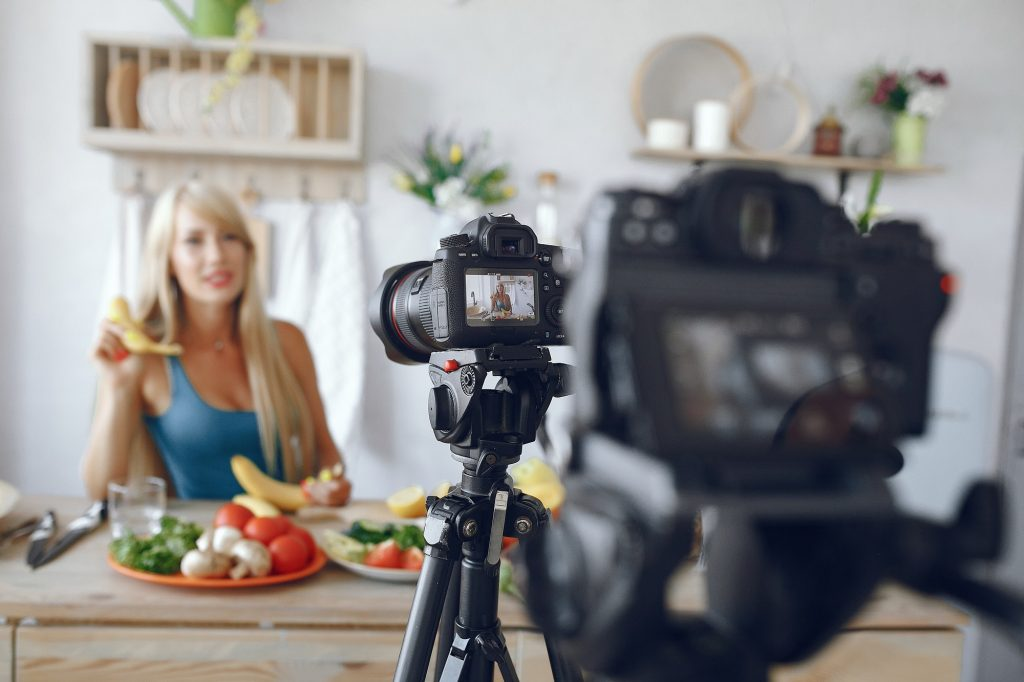 Beautiful and sporty girl in a kitchen recording a video