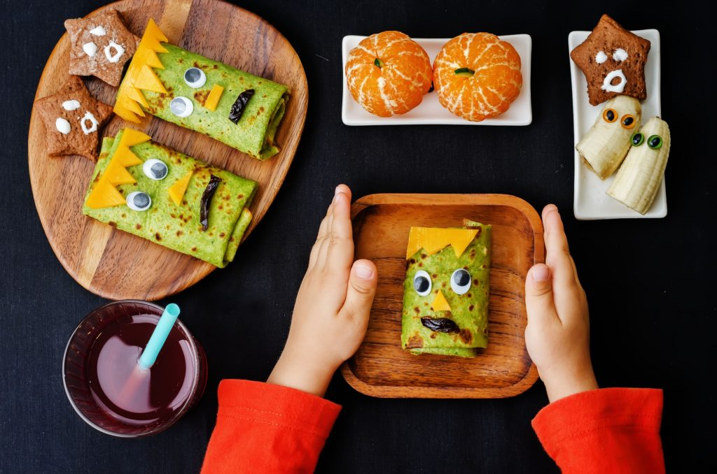 childrens hands holding plate with lunch in the form of monsters