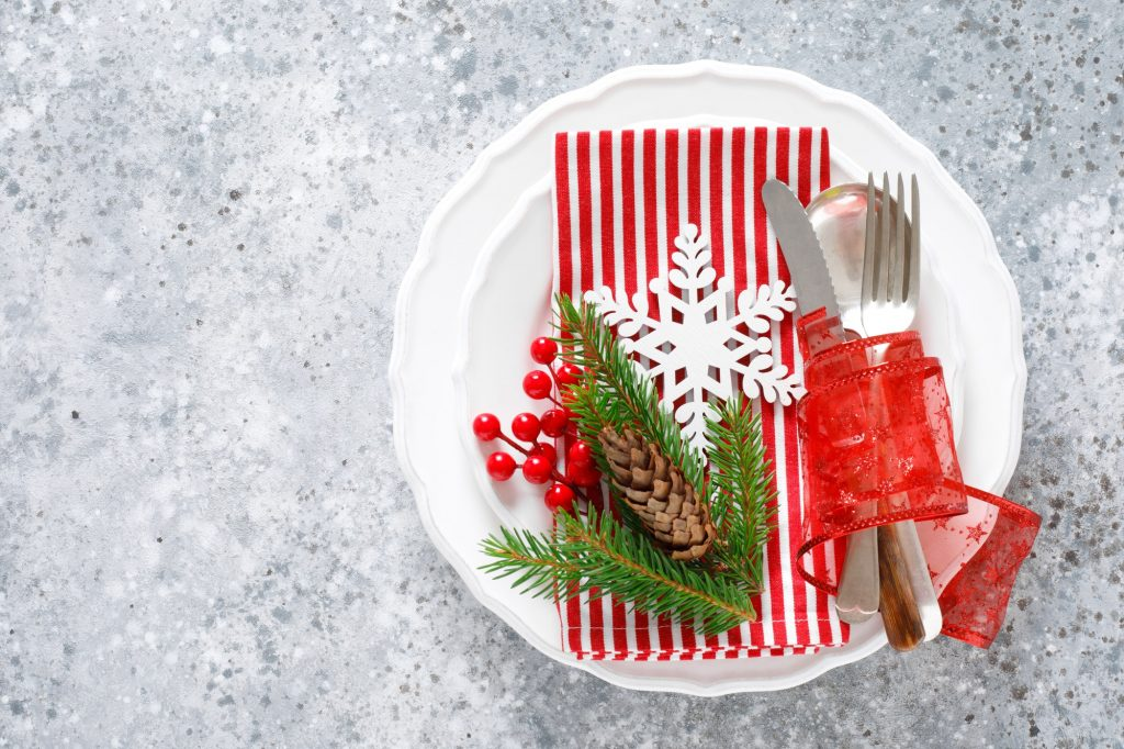 Christmas table setting with empty festive white plate and cutlery
