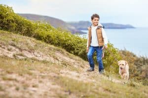 Boy Exercising Dog On Leash Walking Up Hill By Sea