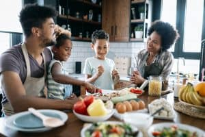 Happy family in the kitchen having fun and cooking together. Healthy food at home