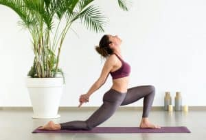 Young woman doing a low lunge yoga exercise