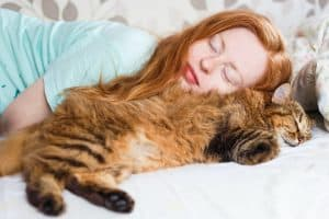 Young redhair woman sleeping with cat.