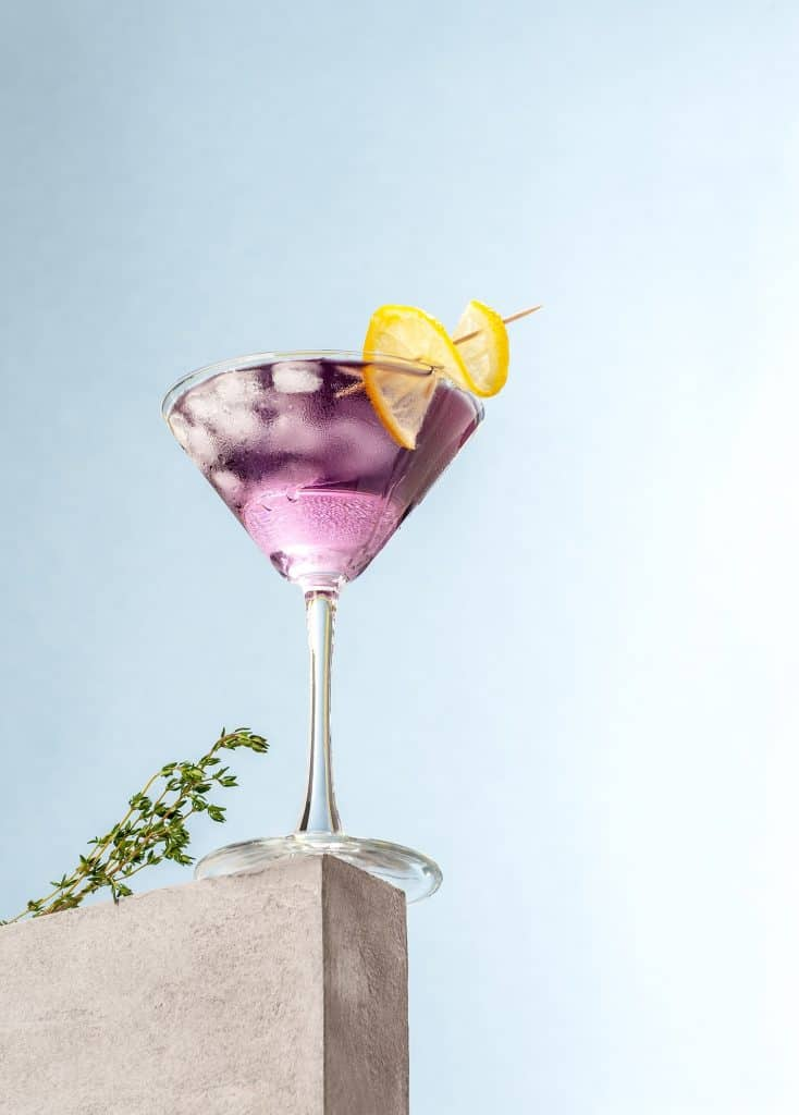 Cold cocktail with lavender syrup and lemon with ice on a light