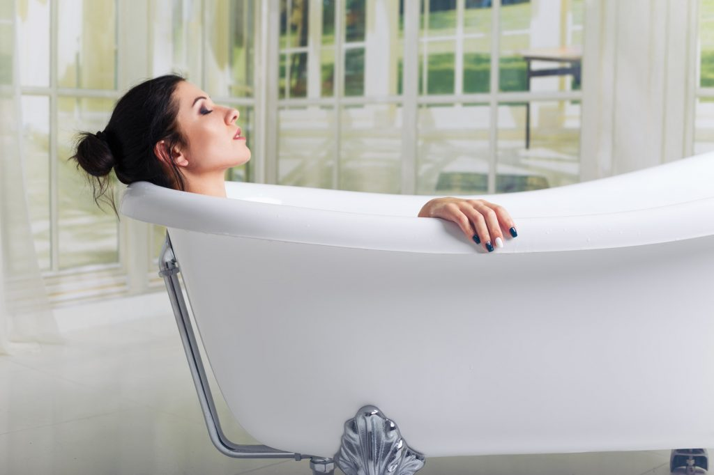 Bathing woman relaxing in bath smiling relaxing with eyes closed