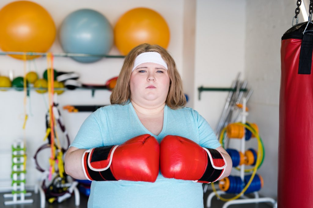 Overweight Woman Boxing in Gym