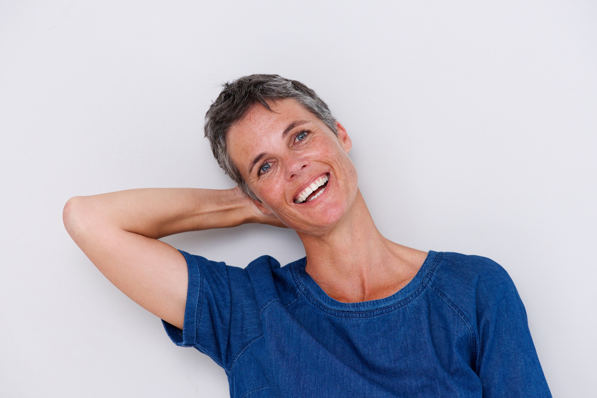 happy older woman with hand behind head