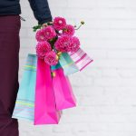 Stylish man holding flowers and pink, blue shopping bags on brick background. Woman's day