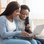Cheerful black women browsing dating website on laptop