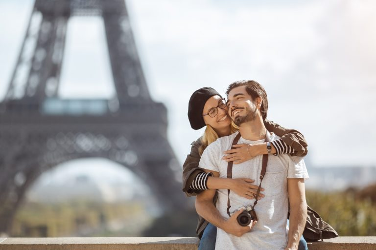 Paris Eiffel tower romantic couple embracing kissing in front of Eiffel Tower, Paris, France