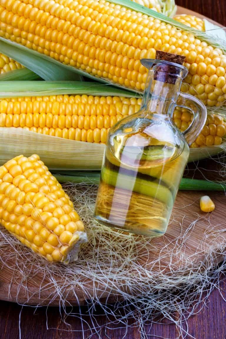 Fresh corn with bottle of oil